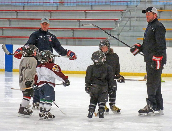 Coaches Ken Mangini and Adam Duskocy working with mini-mites.